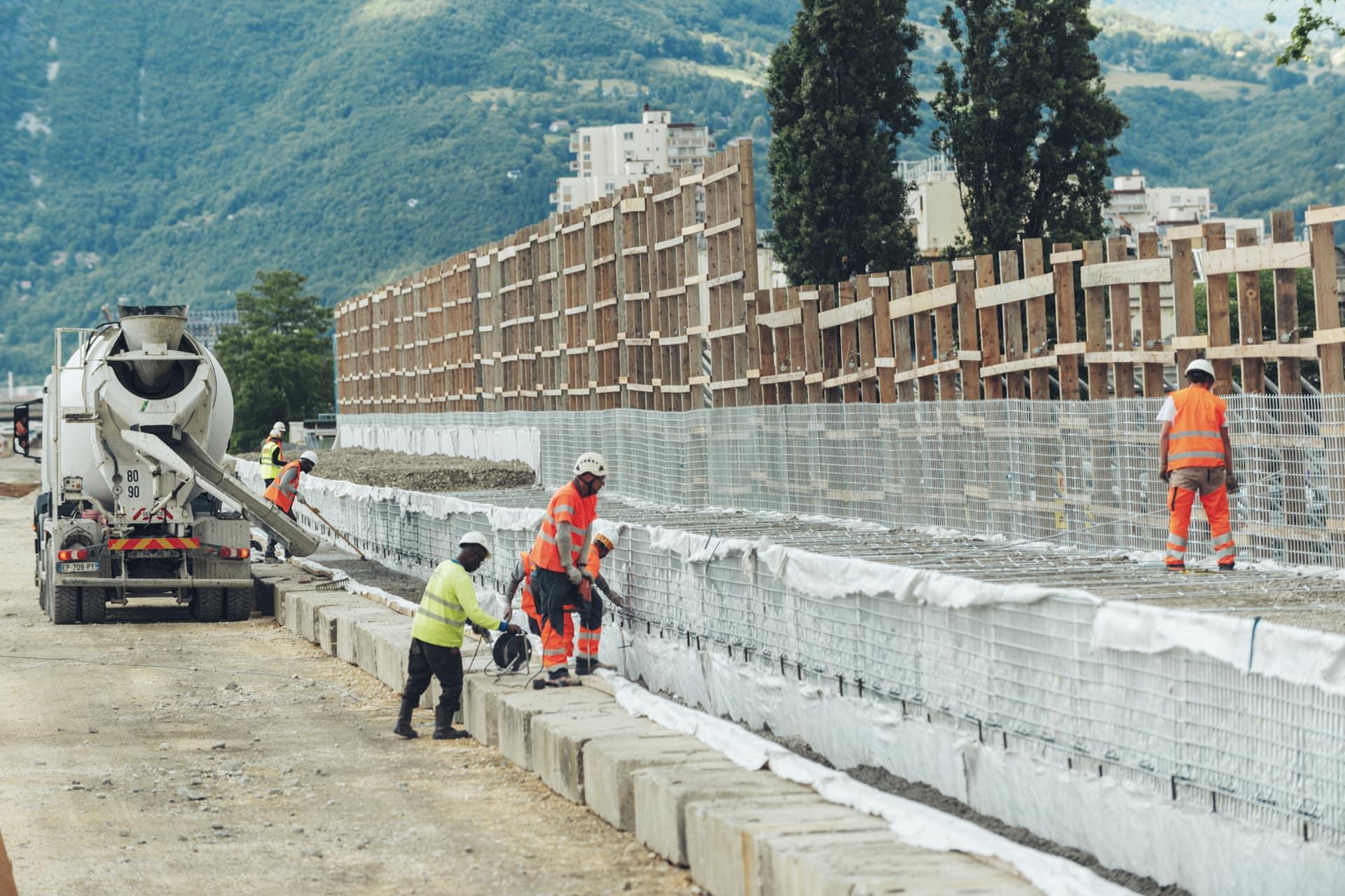 Agents travaillant sur la seconde phase des travaux du mur acoustique au quartier Mistral de Grenoble le long de l'A480