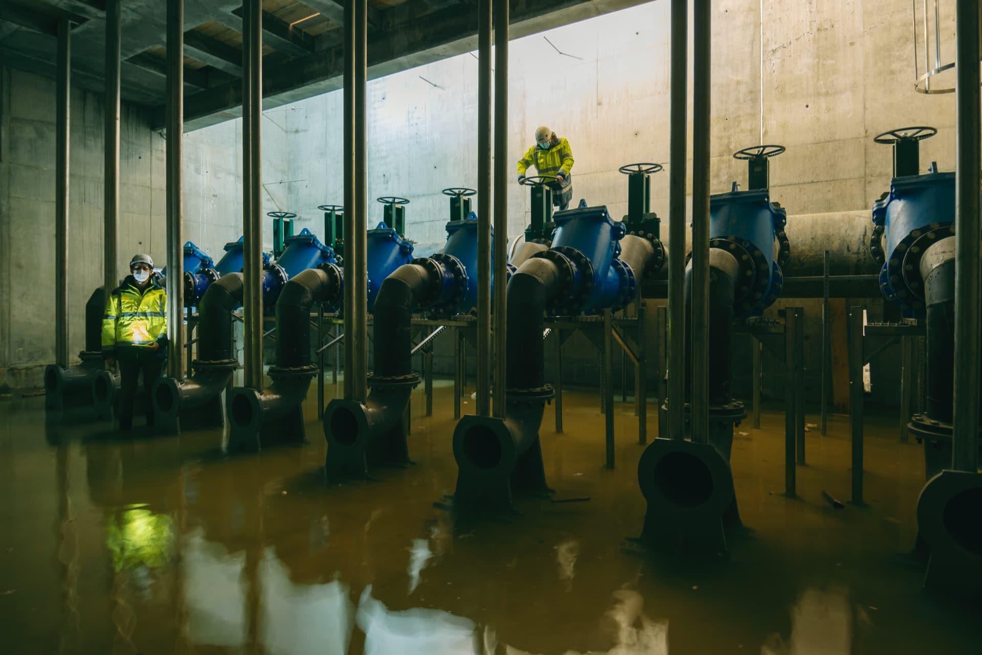 Opérateurs vérifiant le fonctionnement des vannes d'un bassin de traitement de l'autoroute A480