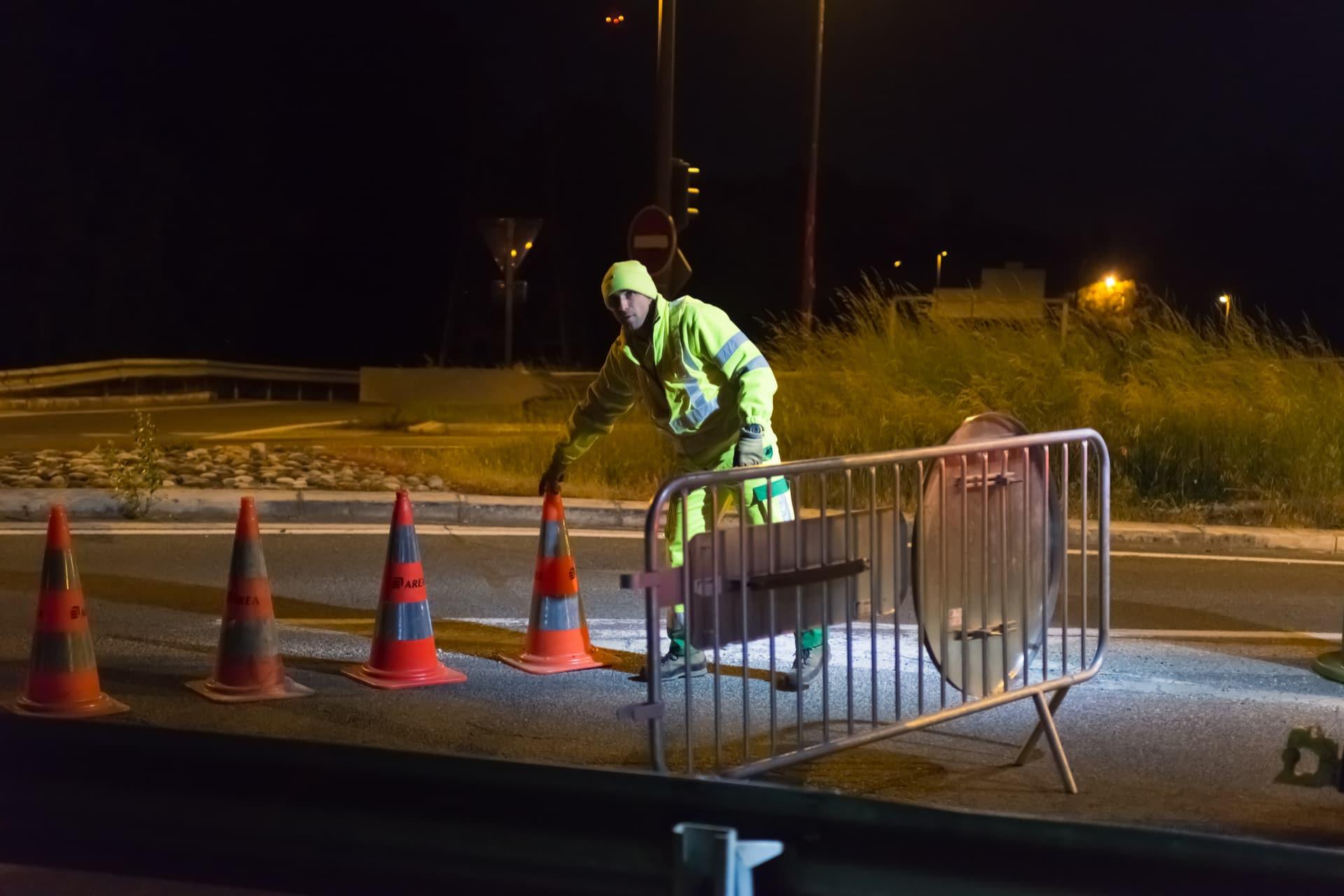 Agent d'AREA mettant en place une signalisation de travaux de nuit