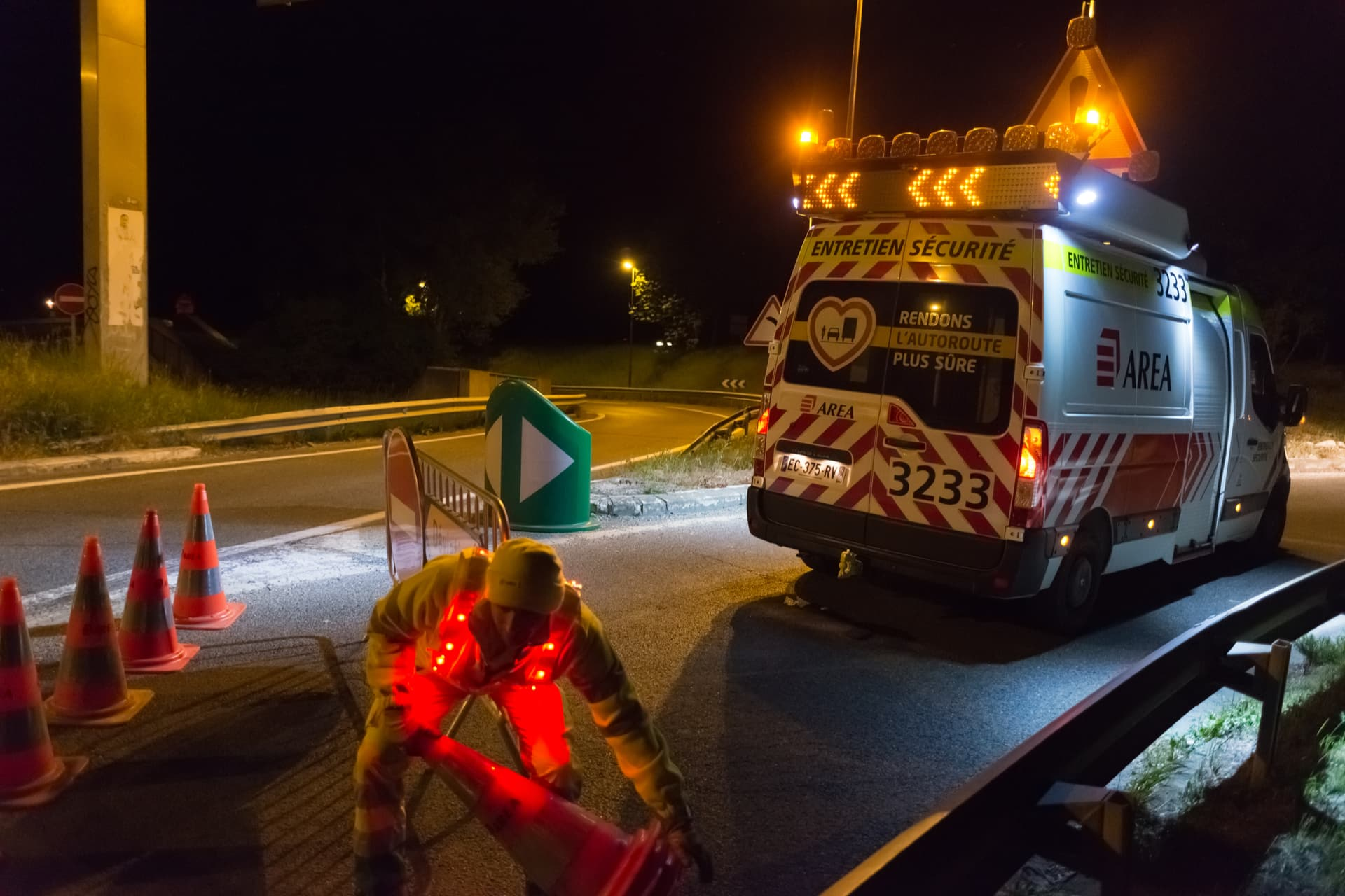 Agent d'AREA installant de nuit une signalisation de travaux